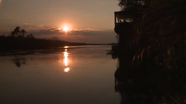 A silhouetted houseboat floats on a river at golden hour. Available in HD.