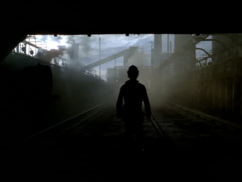 silhouetted industrial worker walks through smoke amongst factory structures, south africa - helm stock-videos und b-roll-filmmaterial
