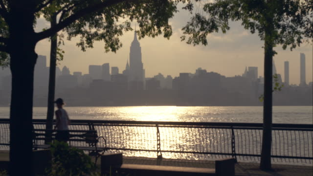 Silhouetted jogger and walker pass through frame at Hudson River waterfront with NYC skyline in background.