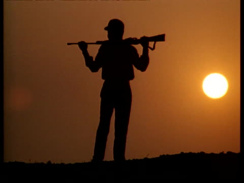 MS Silhouetted man carrying gun wandering against dusk sky with low sun, India