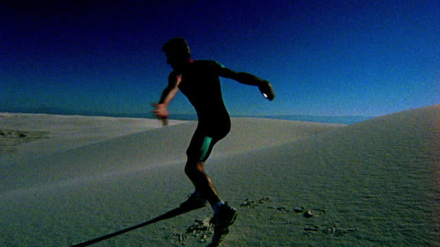 silhouetted man spinning + throwing discus in desert / white sands, new mexico - throwing stock videos & royalty-free footage