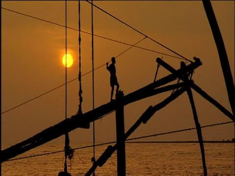 vídeos de stock e filmes b-roll de silhouetted man walks along beam of chinese fishing net contraption at sunset cochin kerala - rede de pesca comercial