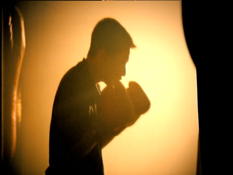 silhouetted man wearing boxing gloves hits punch bag - punch bag stock videos and b-roll footage