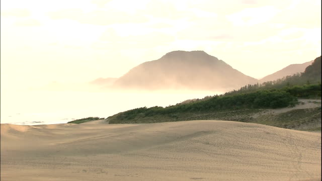 a silhouetted mountain range overlooks the sea of japan and the tottori sand dunes. - ズームアウト点の映像素材/bロール