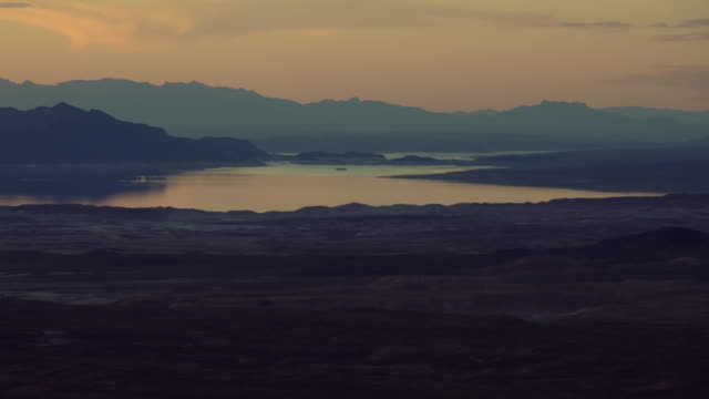 silhouetted mountains surround lake mead. - lake mead video stock e b–roll
