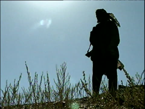 vidéos et rushes de silhouetted northern alliance soldier holding rifle whilst standing on hillside in bamyan region of hazara territory war in afghanistan 2001 - guerre d'afghanistan : de 2001 à nos jours