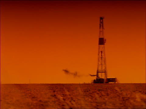 vídeos y material grabado en eventos de stock de silhouetted oil derrick with heat waves + smoke in texas / truck passes in foreground / orange filter - 1996