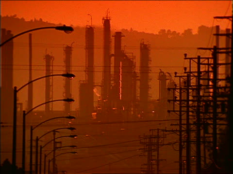 silhouetted oil refinery with telephone poles and lights in foreground at sunset / orange filter / california - cinematography stock videos & royalty-free footage