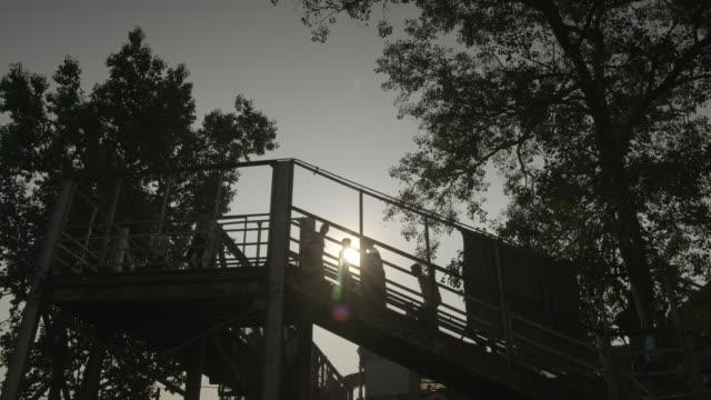 Silhouetted people ascend and descend a railway bridge at sundown, Mumbai, Maharashtra, India.