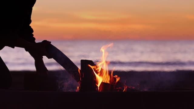 silhouetted person placing logs on beach bonfire - camp fire stock videos & royalty-free footage