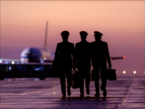 vídeos y material grabado en eventos de stock de silhouetted pilots walking towards stationary aircraft on runway at sunset - pilot