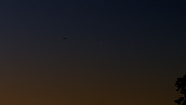 ws silhouetted plane flies over starry night sky - wide shot stock videos & royalty-free footage