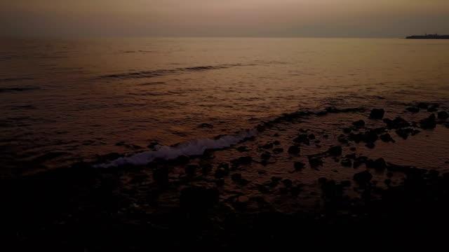 Silhouet stenen op de kust van Maui strand onder zonsondergang