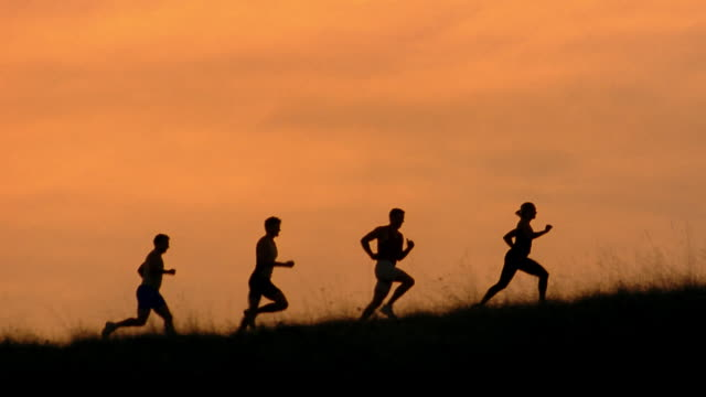 Silhouetted runners jog through a field at golden hour.
