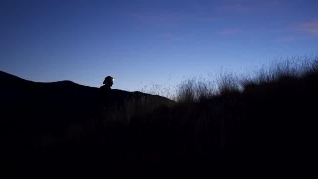 vidéos et rushes de tir silhouetted d'un garde-parc avec la lampe frontale au crépuscule - parc national