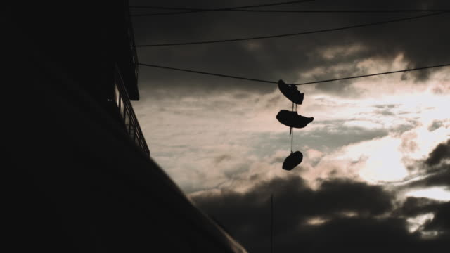 silhouetted sneakers hanging on a power line during a brooklyn sunset - power line点の映像素材/bロール