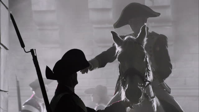 a silhouetted soldier in a french revolution uniform takes orders from a military leader on horseback. - rivoluzione francese video stock e b–roll