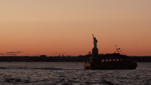 ms silhouetted statue of liberty at sunset with sailboat in foreground - new yorker hafen stock-videos und b-roll-filmmaterial