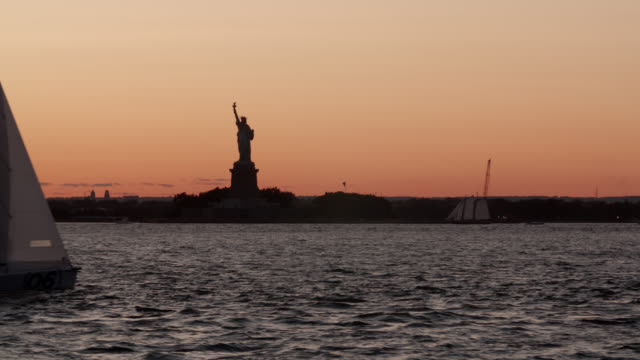 ms silhouetted statue of liberty at sunset with sailboat in foreground - female likeness stock videos & royalty-free footage