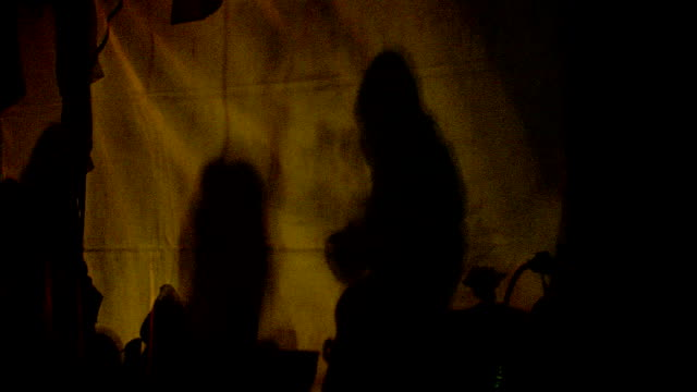 silhouetted survivors walk by a tent cloth illumined by a campfire after the chuetsu earthquake. - テント点の映像素材/bロール