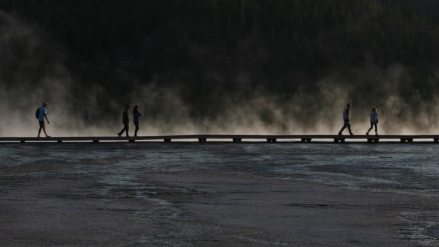 vídeos y material grabado en eventos de stock de silhouetted tourist walking a boardwalk next to a steaming hot spring. - cinco personas