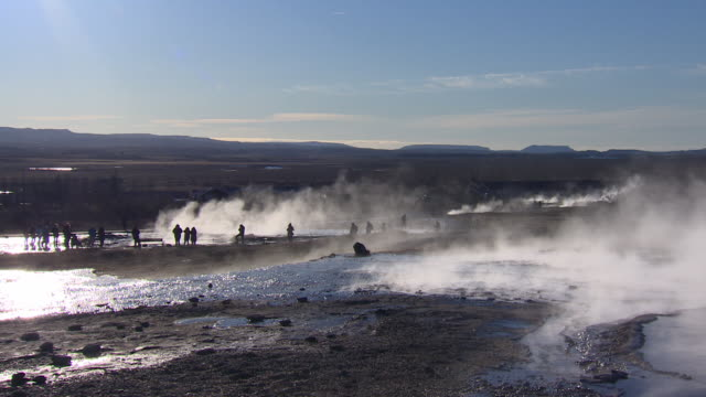 Silhouetted tourists visit a geothermal field in Iceland (with fast zoom).
