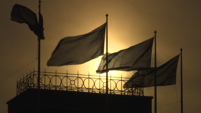 silhouetted union jack flags on the grand building appear black against a red sunset, trafalgar square, london, uk. - flag blowing in the wind stock videos & royalty-free footage