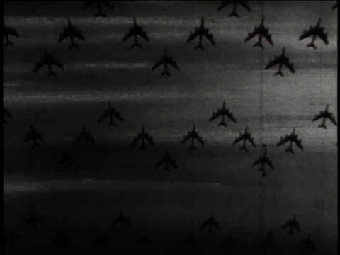 stockvideo's en b-roll-footage met silhouetted united states air force bombers fly through the sky; a video shows the earth and the soviet union's sickle. - koude oorlog