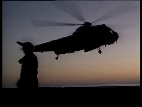 Silhouetted US Navy Chinook lands on USS Eisenhower guided by silhouetted sailors Adriatic Sea 1994