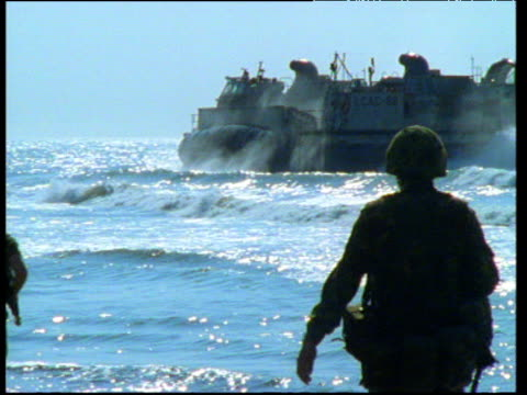 silhouetted us soldiers walk along beach with military hovercraft spraying water skirts in background. - hovercraft stock videos & royalty-free footage
