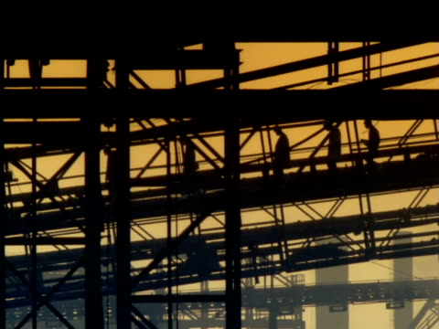 silhouetted workers cross industrial site on footbridge, south africa - getönt stock-videos und b-roll-filmmaterial