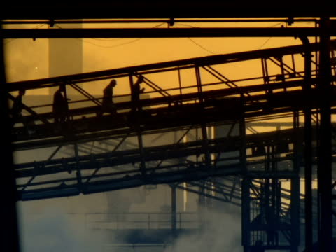 stockvideo's en b-roll-footage met silhouetted workers cross industrial site on footbridge through rising smoke, south africa - sepiakleurig