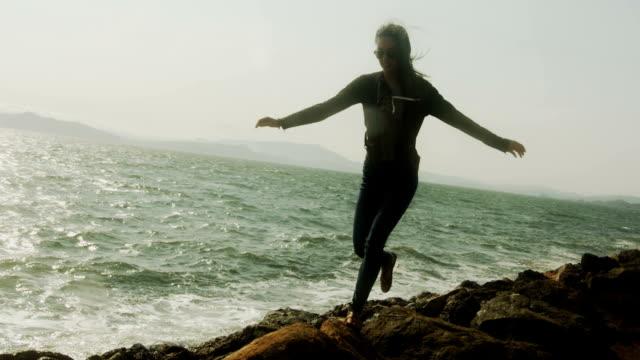 Eine Silhouette junge Frau springt von Fels zu Fels am Wasser.