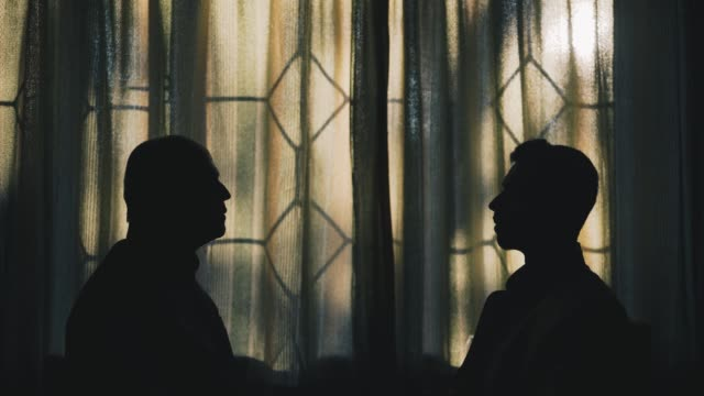 Silhouettes of a Father and Son looking at each other