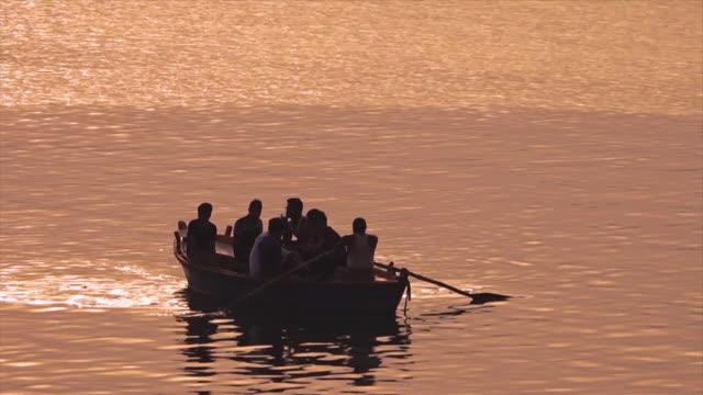 vidéos et rushes de silhouettes of a tourist boat at sun set, ganges - à bord