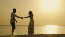 Silhouettes of a young couple, funny dancing against the backdrop of the sea and the setting sun. Merry holiday by the sea
