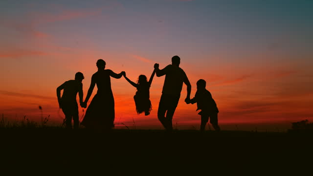 super slo mo silhouettes of a young family having fun jumping in the air on a meadow at dusk - family with three children stock videos & royalty-free footage