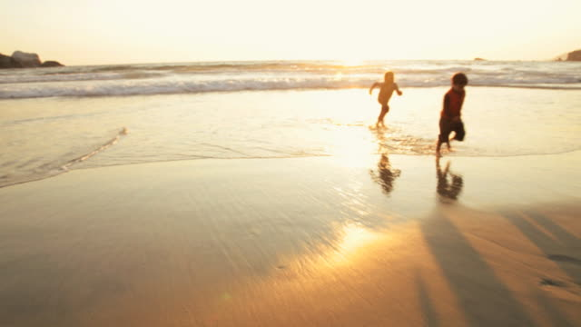 WS Silhouettes of boy (4-5) and girl (6-7) playing on beach at sunset, Big Sur, California, USA