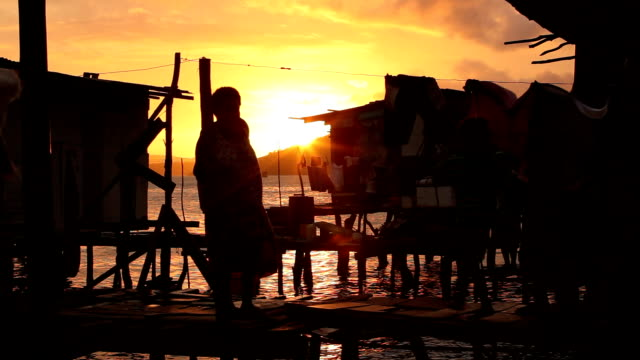 Silhouettes of children and woman walking on bridge to water village at sunset Papua New Guinea is an island located in Oceania There are around 850...