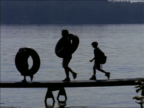 Silhouettes of children + man carrying inner tubes + backpacks walking on dock on lake