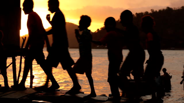 Silhouettes of children walking across bridge to water village at sunset Papua New Guinea is an island located in Oceania There are around 850...