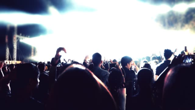 vídeos de stock e filmes b-roll de silhouettes of concert crowd at rear view of festival crowd raising their hands on bright stage lights - evento de entretenimento