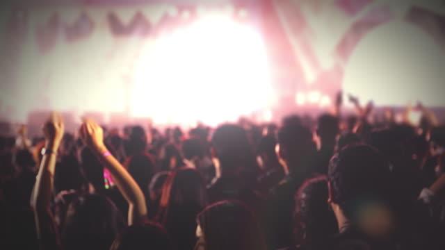 silhouetten des konzertpublikums bei der rückansicht des festivalpublikums, das die hände auf hellen bühnenlichtern hebt - applaudieren stock-videos und b-roll-filmmaterial
