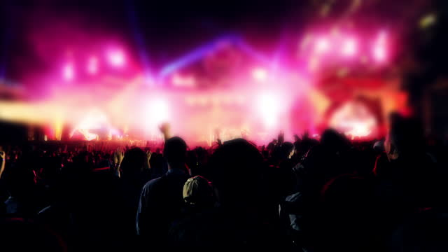 silhouettes of concert crowd at rear view of festival crowd raising their hands on bright stage lights - pop musician stock videos & royalty-free footage