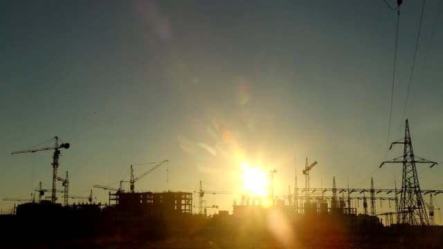 silhouettes of construction cranes at sunset (time lapse)