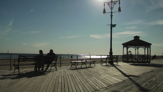 WS, Silhouettes of couple relaxing on bench on boardwalk, Coney Island, New York City, New York, USA