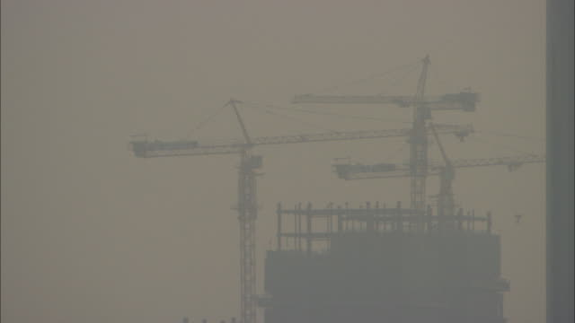 ms silhouettes of cranes atop building under construction, guilin, guangxi zhuang autonomous region, china - guangxi zhuang autonomous region china stock videos & royalty-free footage