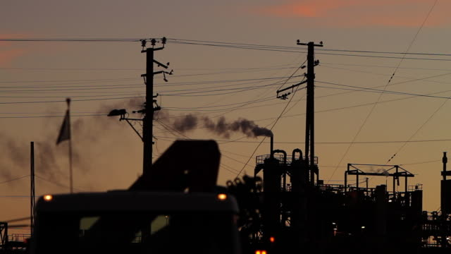ms silhouettes of electric poles and industrial building with smoke coming out of chimney in sunset light with top of truck - travelling light stock videos & royalty-free footage