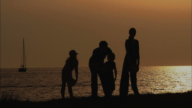 stockvideo's en b-roll-footage met ws tu td silhouettes of family with two children on beach at sunset / slovenia - slovenië