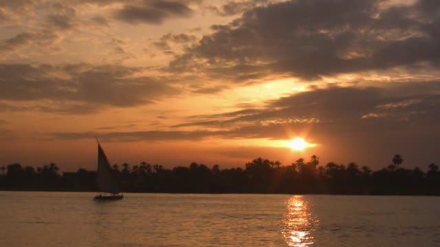 WS, Silhouettes of felucca boat on Nile River at sunset, Cairo, Egypt